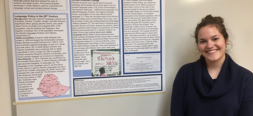 Carly Marten smiling and standing next to a poster of her undergraduate thesis